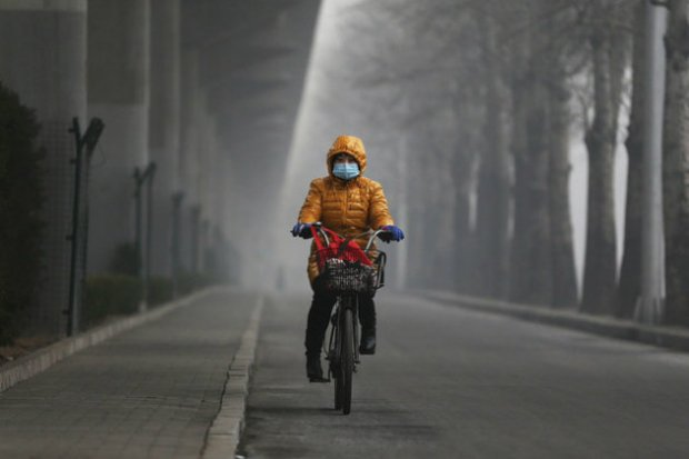 A woman rides her bicycle with a protective mask in Beijing. (Getty Images)