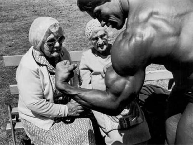 Arnold Schwarzenegger shows off to some elderly women in the 1970's.